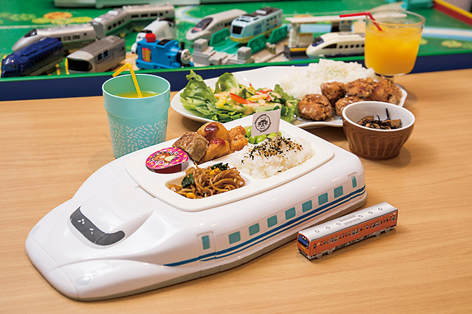 電車形の菓子が付く「新幹線KID'Sプレート」(756円)と「唐揚げプレート」(1,080円)(奥)。
