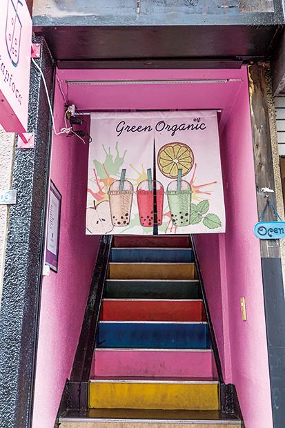 階段まわりもピンク。色鮮やかな暖簾と階段を抜けて店内へ。