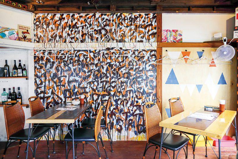 1階は立ち飲みメイン。2階は知人のアーティストがペイントした内装がポップなテーブル席。